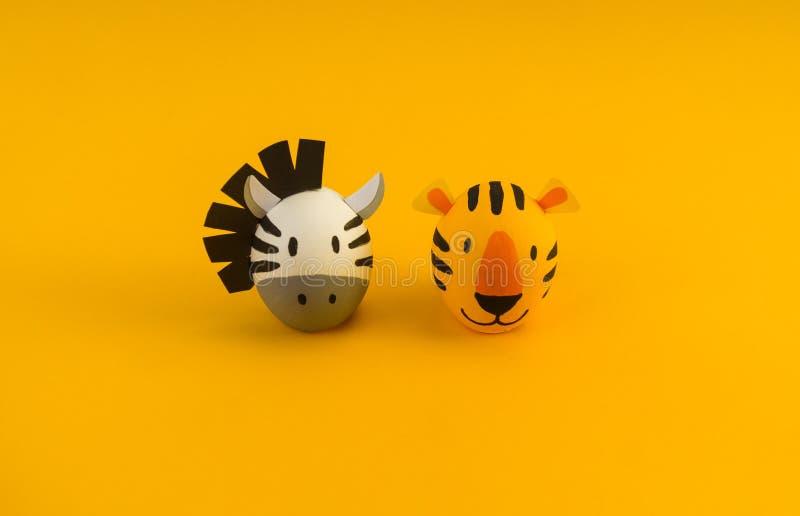 Concetto di festa di Pasqua con le uova fatte a mano sveglie: tigre e zebra arancio immagine stock libera da diritti