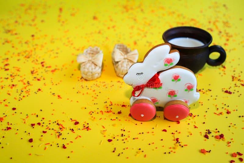 Concetto di festa di Pasqua, pan di zenzero bianco fatto a mano e di rosa sotto forma di coniglietto, bicchiere di latte marrone  fotografia stock