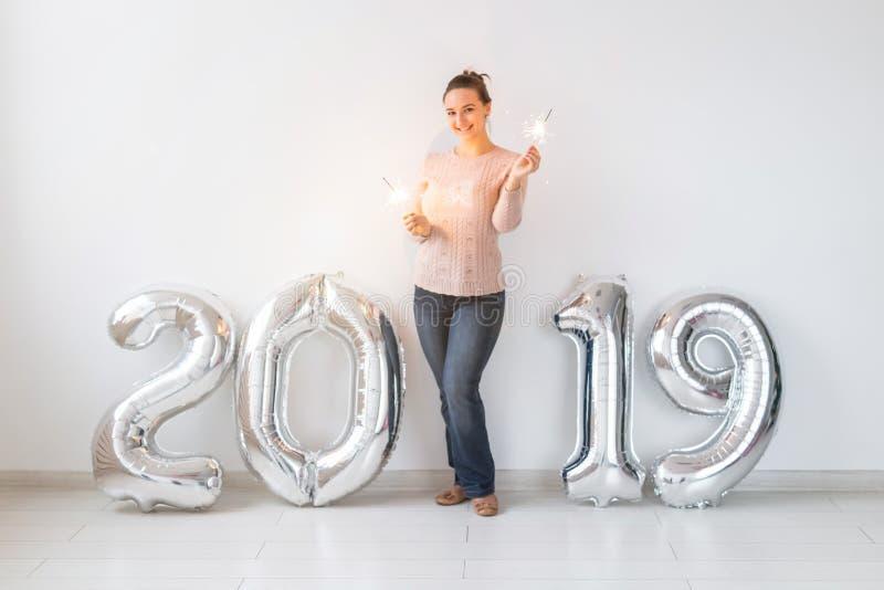 Concetto di feste del partito, della gente e del nuovo anno - donna che celebra vigilie 2019 con e stelle filante dei nuovi anni fotografia stock libera da diritti