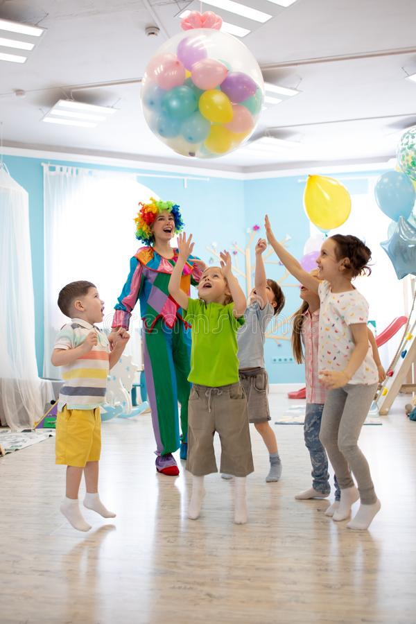 Concetto di feste, di infanzia e di celebrazione - parecchi bambini divertendosi e saltando sulla festa di compleanno nello spett fotografia stock
