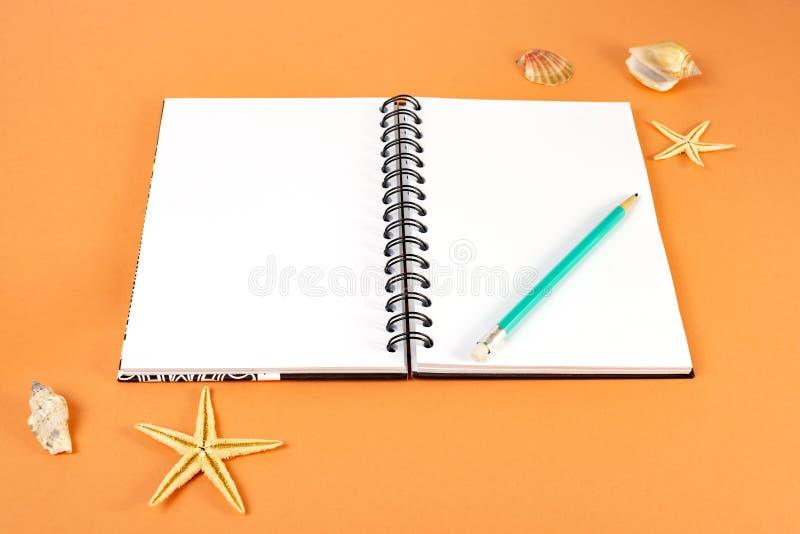 Concetto di feste, di viaggio e di estate - taccuino con la matita e coperture su fondo arancio fotografia stock
