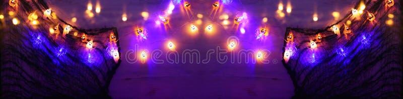 Concetto di festività per lo sfondo di Halloween con la ragnatela e le luci colorate di garland fotografia stock libera da diritti