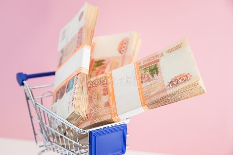 Concetto di finanza, carrello con soldi carrello di compera e soldi russi Concetto di affari, investimento sbagliato immagini stock