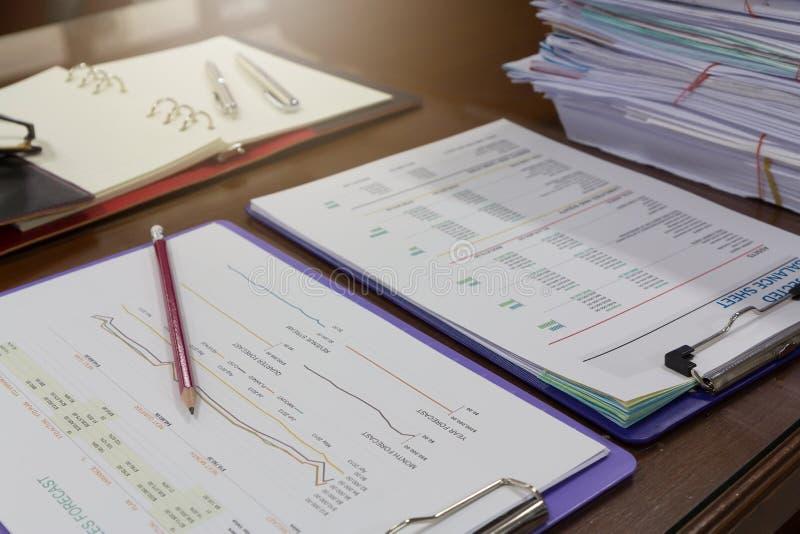 Concetto di finanza e di affari del grafico di analisi sulla scrivania con la pila di carte d'ufficio immagini stock