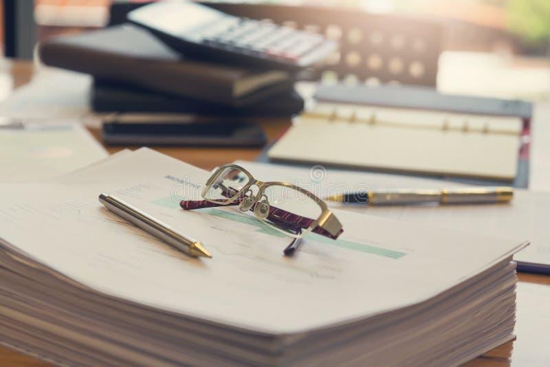 Concetto di finanza e di affari di funzionamento dell'ufficio, degli occhiali del primo piano e della penna sulla pila di documen fotografia stock libera da diritti