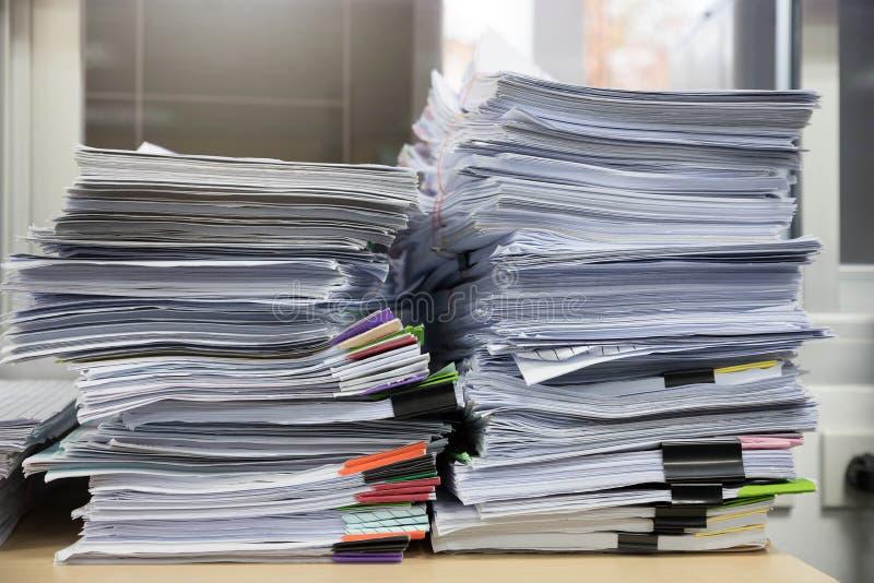 Concetto di finanza e di affari di funzionamento dell'ufficio, mucchio dei documenti non finiti sulla scrivania, pila di carte d' immagine stock
