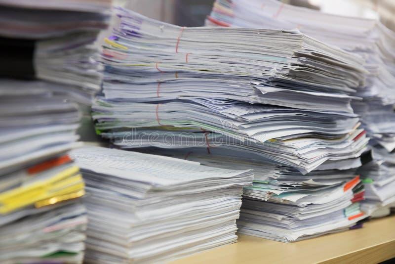 Concetto di finanza e di affari di funzionamento dell'ufficio, mucchio dei documenti non finiti sulla scrivania, pila di carte d' fotografia stock libera da diritti