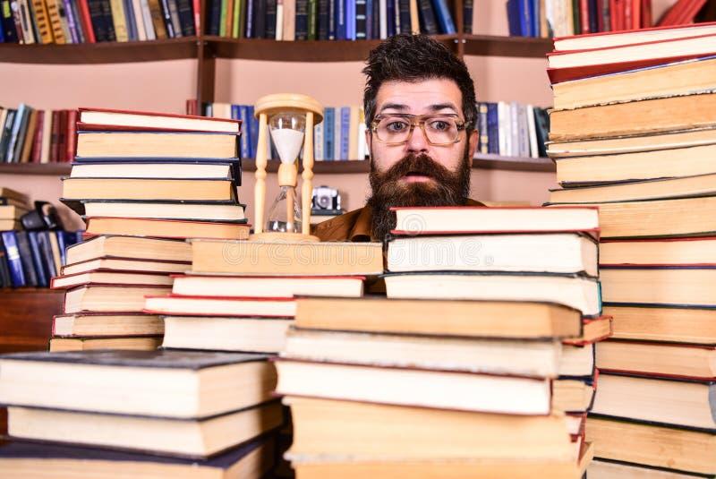 Concetto di flusso di tempo Insegnante o studente con la barba che studia nella biblioteca L'uomo, scienziato in vetri esamina la fotografie stock