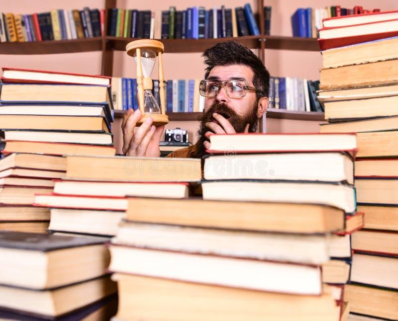 Concetto di flusso di tempo Insegnante o studente con la barba che studia nella biblioteca L'uomo, scienziato in vetri esamina la fotografia stock libera da diritti