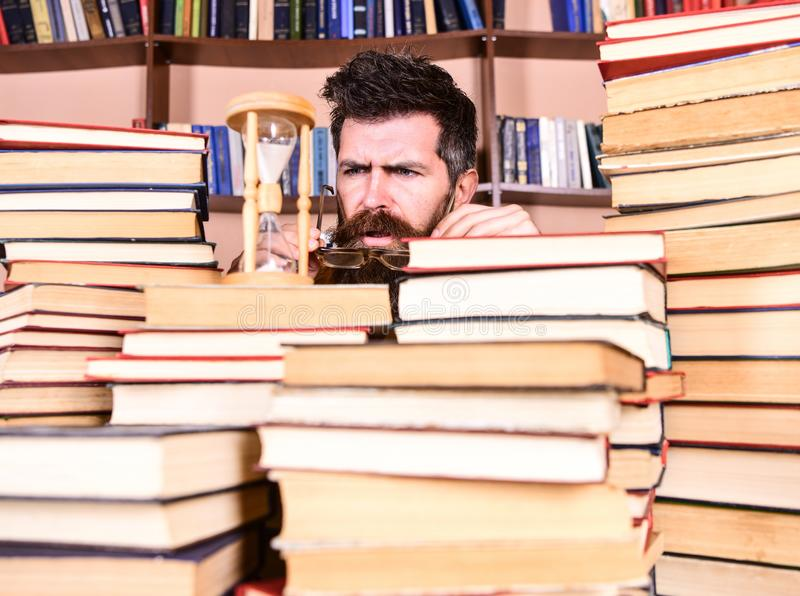 Concetto di flusso di tempo L'uomo, scienziato in vetri esamina la clessidra Insegnante o studente con la barba che studia nella  immagine stock libera da diritti