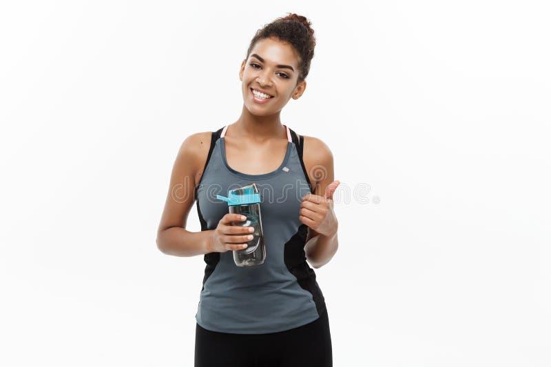 Concetto di forma fisica e sano - la bella ragazza afroamericana nello sport copre la bottiglia di acqua della tenuta dopo l'alle immagini stock libere da diritti