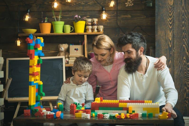 Concetto di formazione Gioco del gioco da bambini con la madre ed il padre, istruzione Istruzione e supporto di babysitter della  fotografie stock libere da diritti