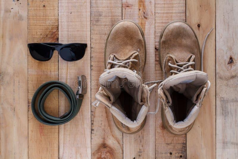 Concetto di fotografia di arte di natura morta con gli stivali, la cinghia e i sunglass immagini stock libere da diritti