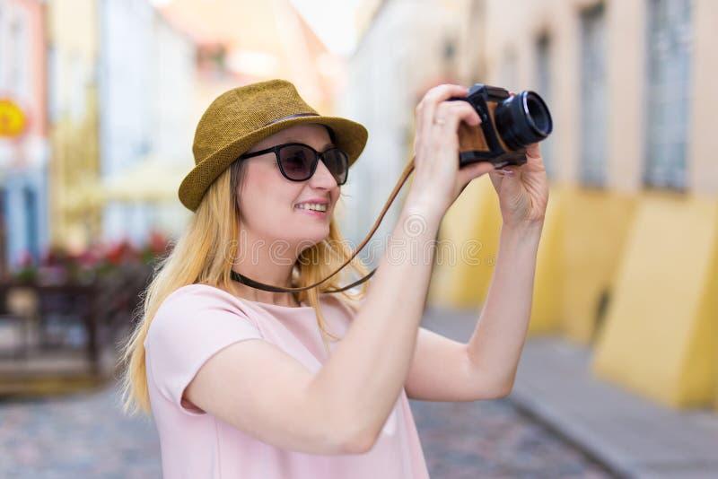 Concetto di fotografia e di viaggio - turista della giovane donna con la macchina fotografica immagini stock