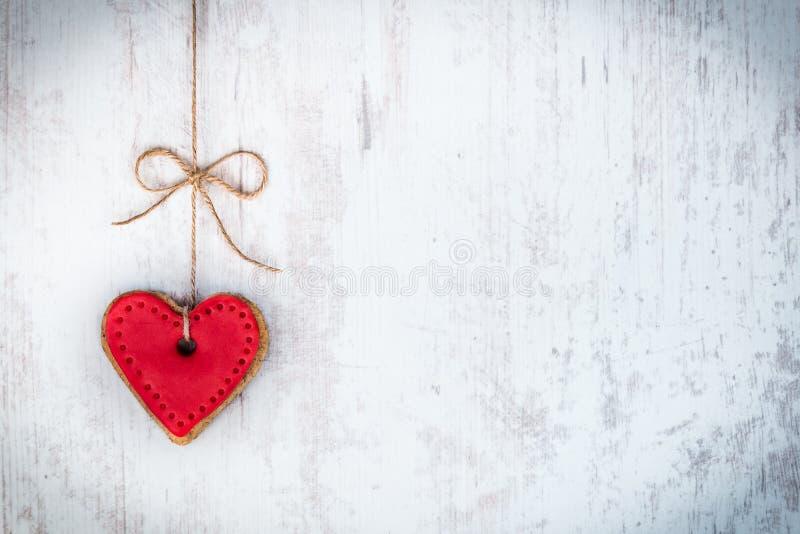 Concetto di giorno dei biglietti di S Il cuore ha modellato il biscotto legato con l'arco della canapa sopra fondo rustico di leg immagine stock libera da diritti
