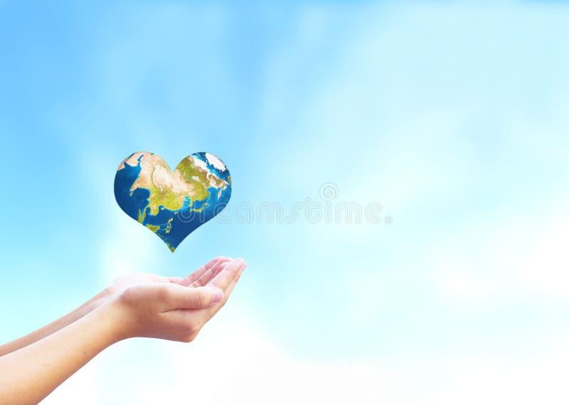 Concetto di giorno del cuore del mondo: l'uomo apre le palme e trascina le piante verdi a forma di cuore fotografie stock libere da diritti