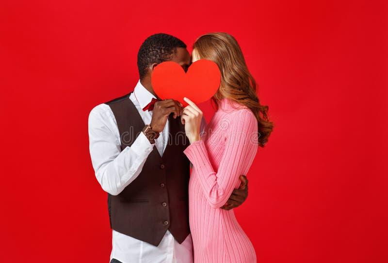 Concetto di giorno del ` s del biglietto di S giovani coppie felici con cuore su rosso immagini stock