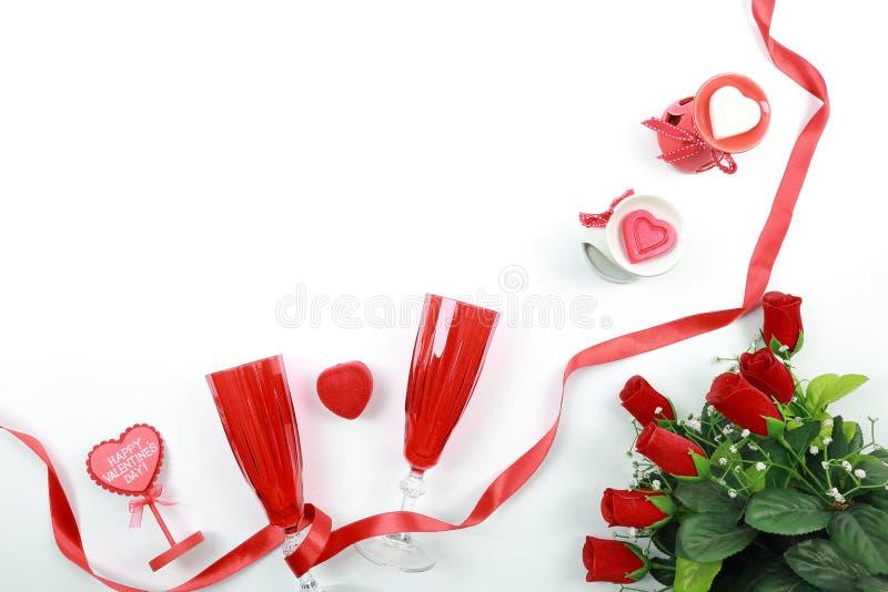 Concetto di giorno del ` s del biglietto di S Il vetro rosso del champagne con il nastro ed il cuore rossi ha modellato le candel immagine stock libera da diritti