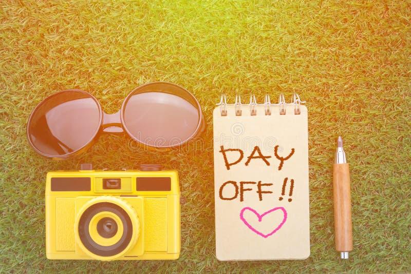 Concetto di giorno libero con la macchina fotografica del taccuino di vetro di sole e il penci tagliente immagine stock