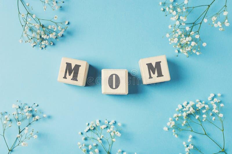 Concetto di giorno di madri, cartolina d'auguri con la mamma di parola sui cubi del giocattolo e fiori immagini stock