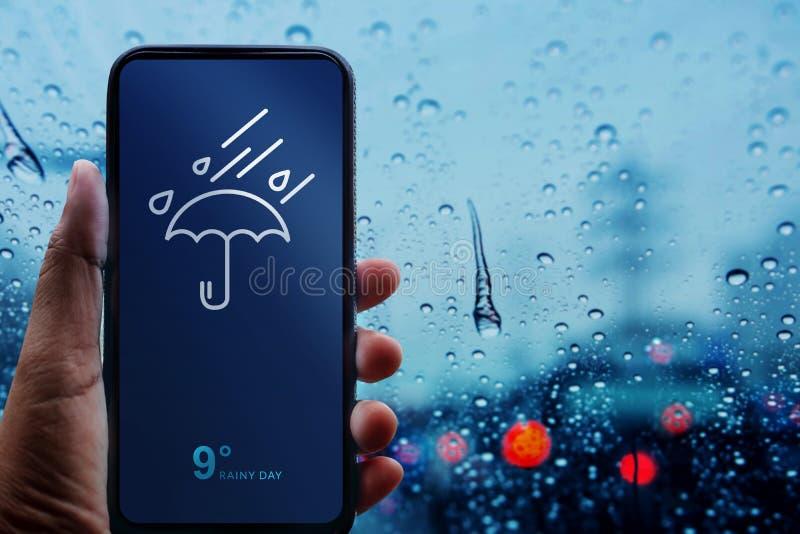 Concetto di giorno piovoso Mano che tiene Smartphone con tempo Informat fotografie stock
