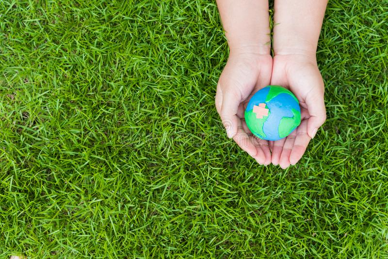 Concetto di giorno di terra del mondo Mano della donna che tiene globo fatto a mano immagine stock libera da diritti