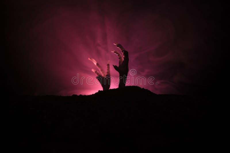 Concetto di Halloween, mano dello zombie che aumenta fuori dalla terra o mano dello zombie che esce dalla sua tomba fotografie stock