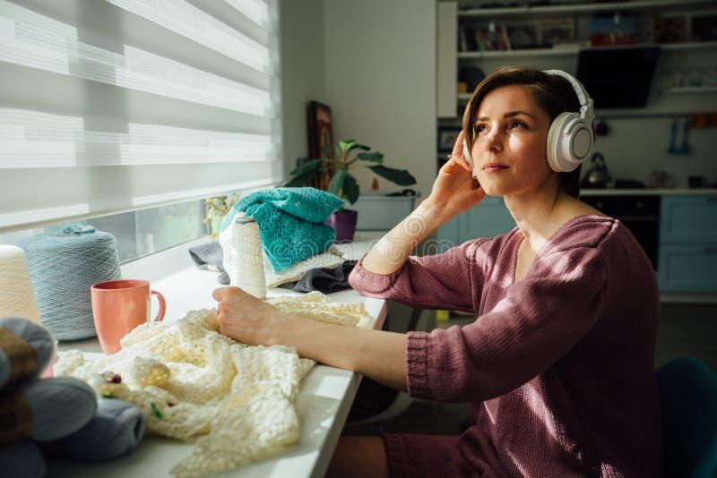 Concetto di hobby, di umore e di svago La donna che si rilassa con le cuffie mentre tricotta il vestito tenero con lavora all'unc immagini stock libere da diritti