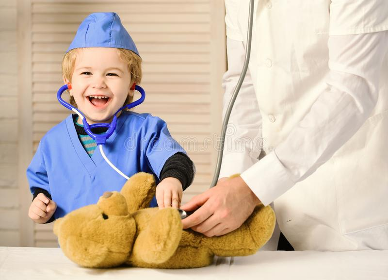 Concetto di infanzia e di salute Il bambino con il fronte felice gioca al dottore fotografia stock