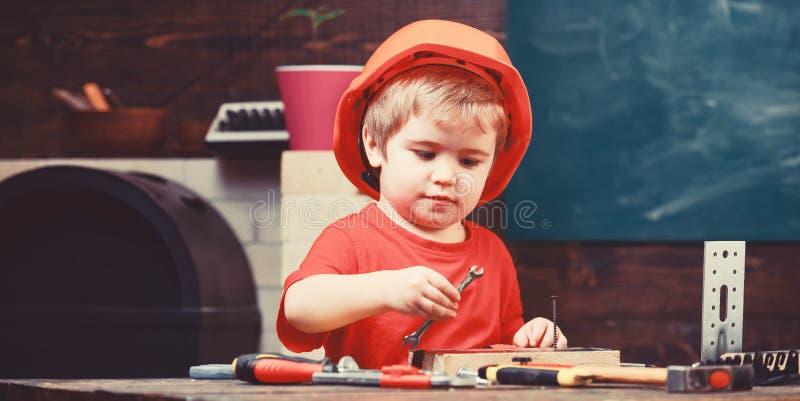 Concetto di infanzia Gioco del ragazzo come il costruttore o riparatore, lavoro con gli strumenti Scherzi il ragazzo in casco o i fotografia stock libera da diritti
