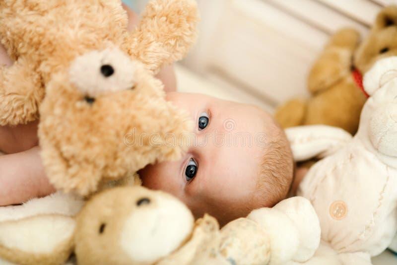 Concetto di innocenza e di infanzia Bambino coperto di suo orsacchiotto fotografia stock libera da diritti