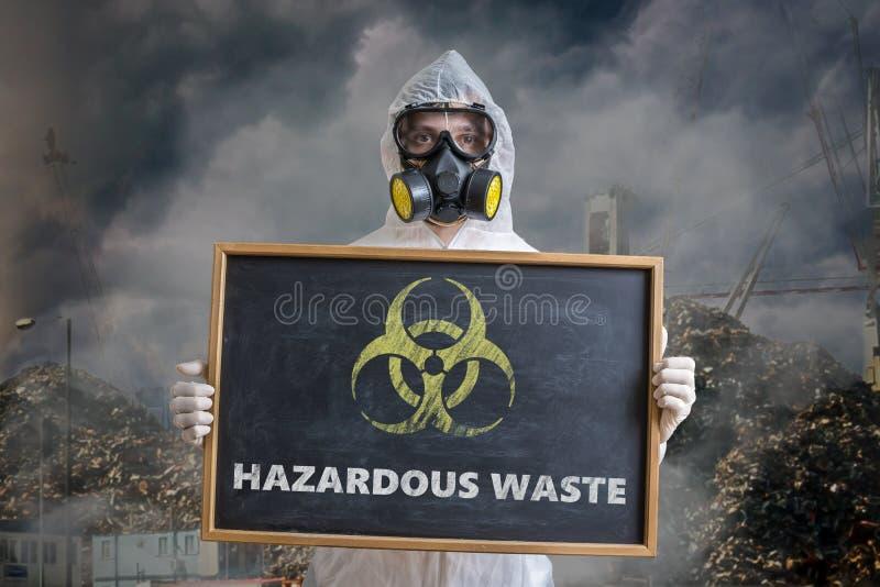 Concetto di inquinamento e di ecologia L'uomo in tute sta mettendo in guardia contro i rifiuti pericolosi fotografie stock