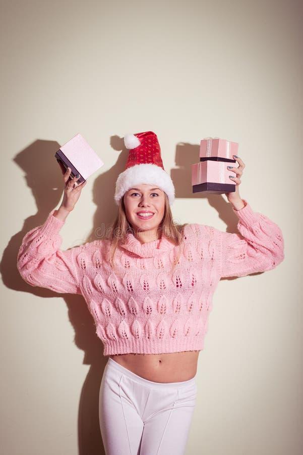 Concetto di inverno di Natale felice - femmina sorridente in cappello dell'assistente di Santa con molti contenitori di regalo fotografia stock