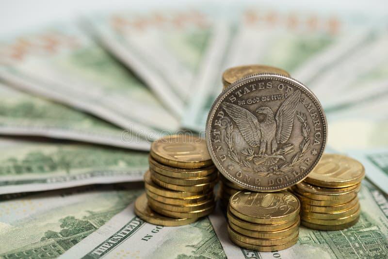 Concetto di investimento - vecchia moneta del dollaro d'argento sulle fatture del dollaro americano fotografia stock libera da diritti