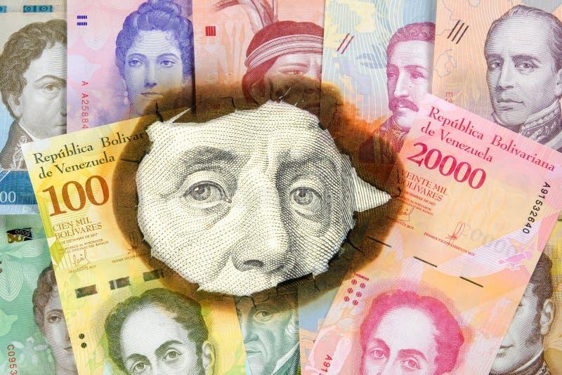 Concetto di iperinflazione Venezuela Soldi venezuelani bruciati con l'immagine degli statisti, attraverso il foro in cui potete v immagine stock