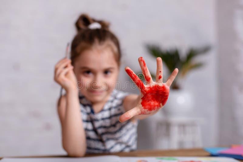 Concetto di istruzione, della scuola, di arte e della pittura - piccola ragazza sorridente dello studente che mostra le mani dipi fotografie stock
