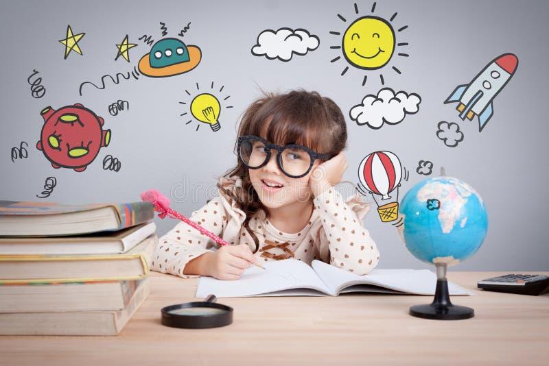 Concetto di istruzione, piccola ragazza felice sveglia alla scuola che fa compito con creatività immagine stock libera da diritti