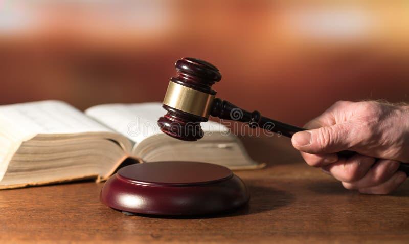 Concetto di legge con la mano che tiene un martelletto del giudice fotografie stock