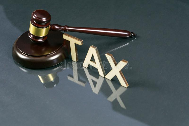 Concetto di legge fiscale La parola accusa il martelletto ed i soldi sulla tavola fotografia stock libera da diritti