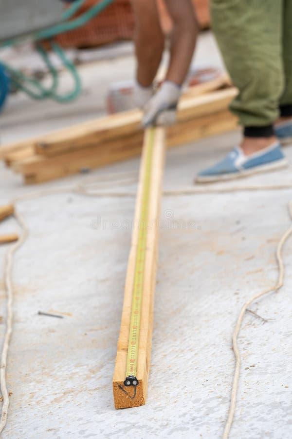 Concetto di legno di alta qualità La fine verticale sulla foto potata dell'estremità del nastro di misurazione è riparata sul bor fotografia stock libera da diritti