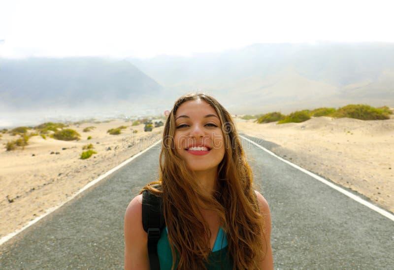 Concetto di libertà Ritratto della giovane donna in mezzo alla strada principale della strada asfaltata del deserto nell'isola di fotografia stock
