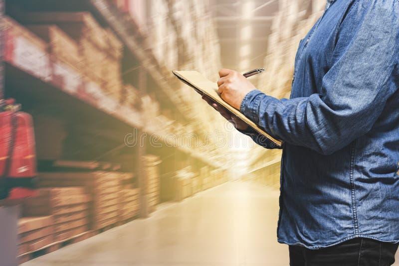 Concetto di logistica di affari, responsabile dell'uomo d'affari che prende le note durante il controllo ed il controllo in magaz fotografia stock