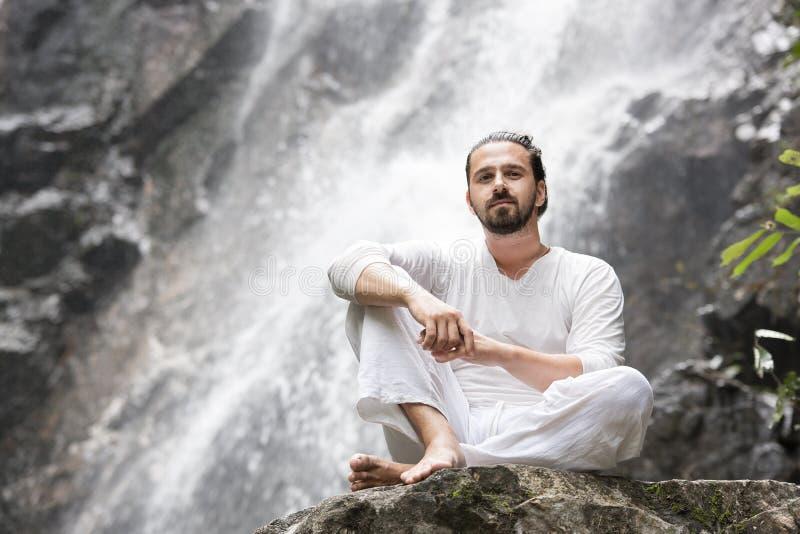 Concetto di meditazione di yoga di benessere Giovane che si siede nella posizione di loto sulla roccia sotto la cascata tropicale fotografia stock libera da diritti