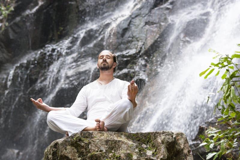 Concetto di meditazione di yoga di benessere Giovane che si siede nella posizione di loto sulla roccia sotto la cascata tropicale immagine stock