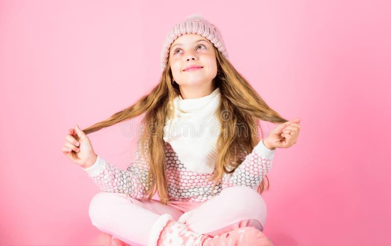 Concetto di modo di inverno Capelli lunghi della ragazza che si rilassano fondo rosa Modello di moda sorridente del bambino Svegl immagine stock libera da diritti