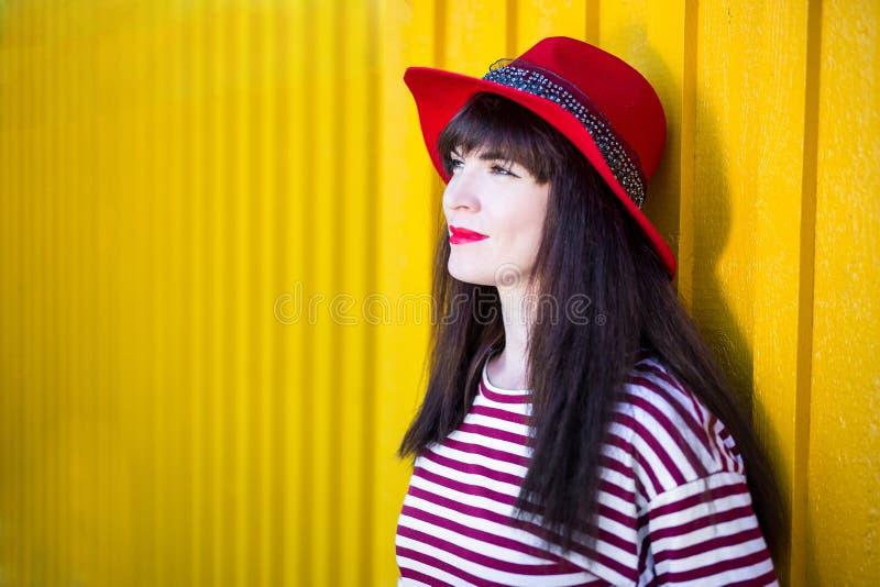 Concetto di modo - ritratto della giovane donna nella posa rossa sopra il yel fotografia stock