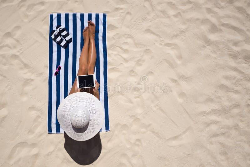 Concetto di modo di vacanza estiva - cappello d'uso d'abbronzatura a del sole della donna fotografia stock