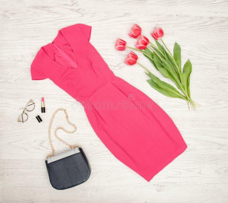 Concetto di modo Vestito cremisi, borsa, rossetto, vetri e tulipani rosa Vista superiore, fondo di legno leggero fotografie stock libere da diritti