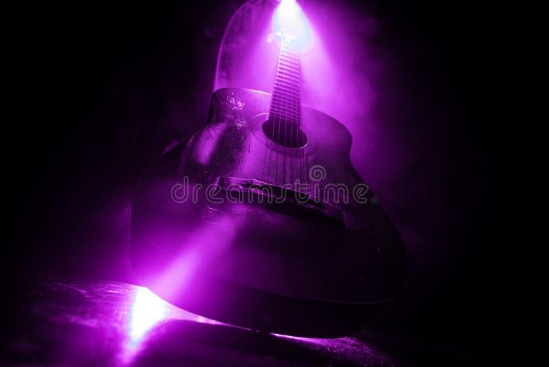 Concetto di musica Chitarra acustica isolata su un fondo scuro nell'ambito del fascio luminoso con fumo con lo spazio della copia fotografie stock