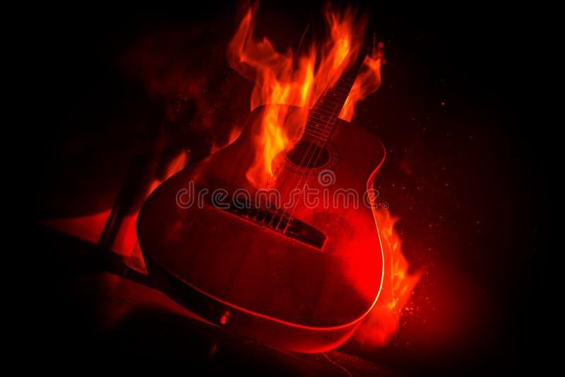Concetto di musica Chitarra acustica isolata su un fondo scuro nell'ambito del fascio luminoso con fumo con lo spazio della copia fotografia stock